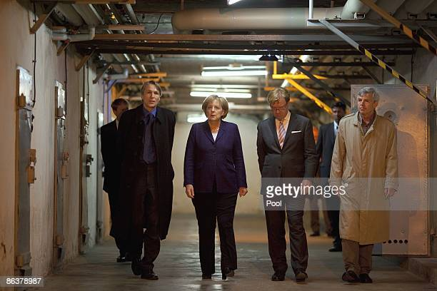 German Chancellor Angela Merkel speaks to current prison memorial director Hubertus Knabe State Secretary Andre Schmitz and former inmate Gilbert...