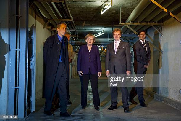 German Chancellor Angela Merkel speaks to current prison memorial director Hubertus Knabe and State Secretary Andre Schmitz while touring the former...