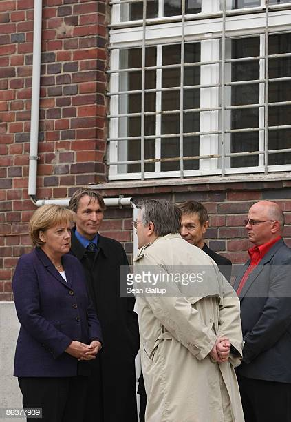 German Chancellor Angela Merkel speaks to former prison inmates Uwe Haedrich Manfred Haferburg and Mirko Roewer while touring the former prison of...