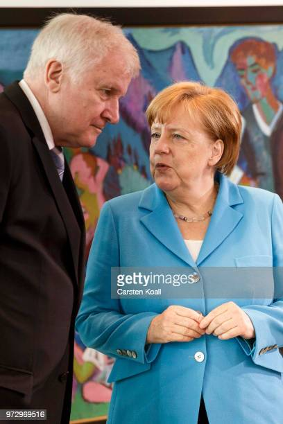 German Chancellor Angela Merkel speaks to German Interior Minister Horst Seehofer after the arrival for the weekly government cabinet meeting on June...
