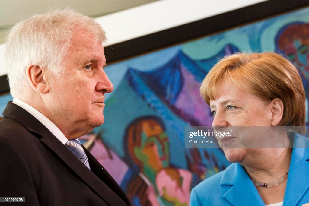 German Chancellor Angela Merkel speaks to German Interior Minister Horst Seehofer after the arrival for the weekly government cabinet meeting on June 13, 2018 in Berlin, Germany. High on the morning's agenda is labour legislation intended to ease workers' transition from part-time to full-time work.