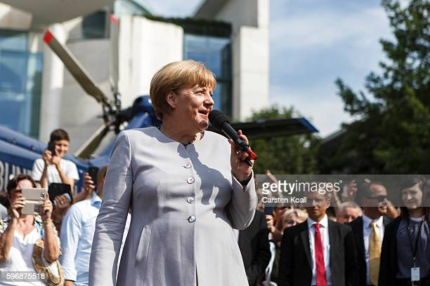 German Chancellor Angela Merkel speaks to members of the public who had come for the annual openhouse day at the Chancellery on August 28 2016 in...
