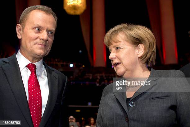 German Chancellor Angela Merkel speaks to Prime Minister of Poland Donald Tusk as they arrive for the opening event of the world's largest computer...