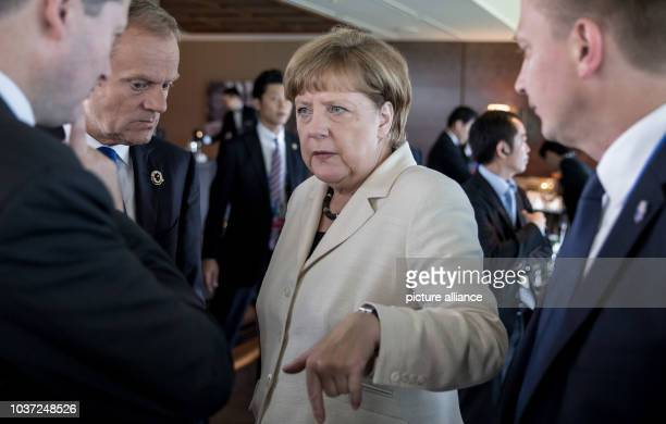 German chancellor Angela Merkel speaks to the President of the European Council Donald Tusk at the beginning of a session at the G7 Ise-Shima Summit...