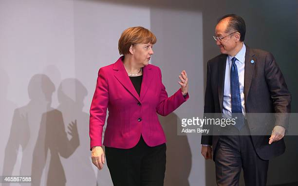 German Chancellor Angela Merkel speaks to World Bank Group President Jim Yong Kim as they arrive for a meeting at the German federal Chancellery on...