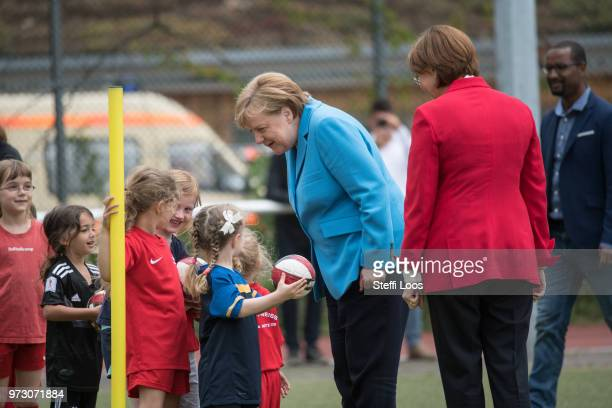 German Chancellor Angela Merkel speaks to young girls during a visit of a program to encourage integration of children with foreign roots through...