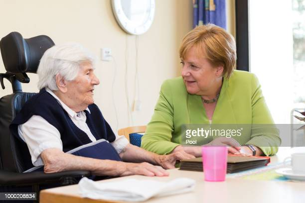 German Chancellor Angela Merkel speaks with residents during a visit to the St Johannesstift senior care facility on July 16 2018 in Paderborn...