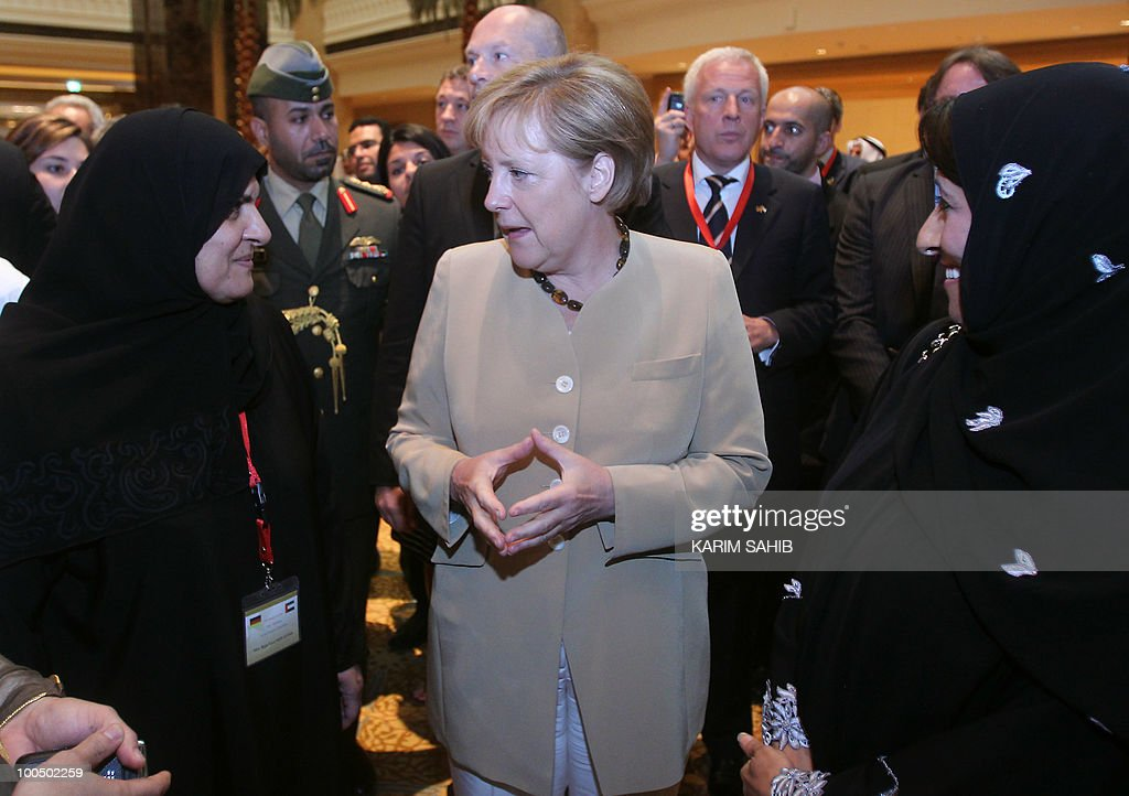 German Chancellor Angela Merkel (C) speaks with Emirati women following a meeting of the UAE-Germany Joint Economic Commission in Abu Dhabi on May 25, 2010. Merkel, who arrived in Abu Dhabi on May 24 for the first leg of a four-nation Gulf tour, has signed a series of accords, including on hydrocarbon sector cooperation.