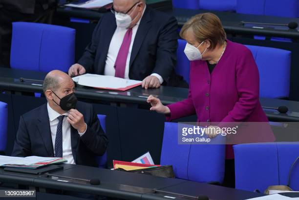 German Chancellor Angela Merkel speaks with Finance Minister Olaf Scholz after she gave a government declaration at the Bundestag prior to today's...