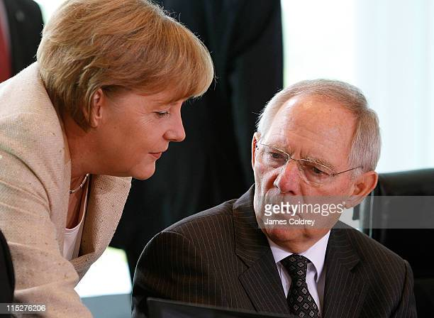 German Chancellor Angela Merkel speaks with Finance Minister Wolfgang Schaeuble upon her arrival at the weekly German government cabinet meeting on...