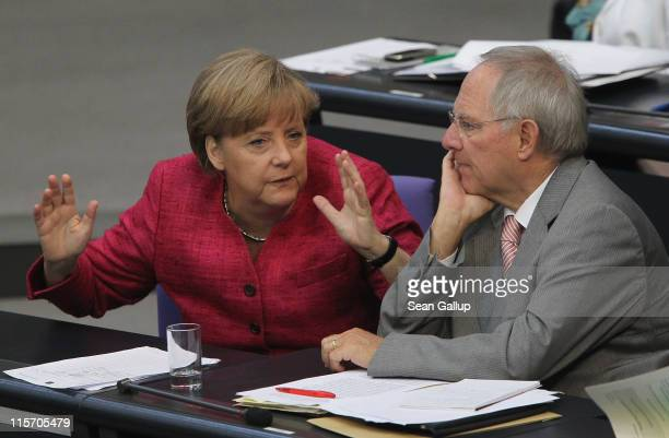 German Chancellor Angela Merkel speaks with Finance Minister Wolfgang Schaeuble after she gave a government declaration at the Bundestag on Germany's...