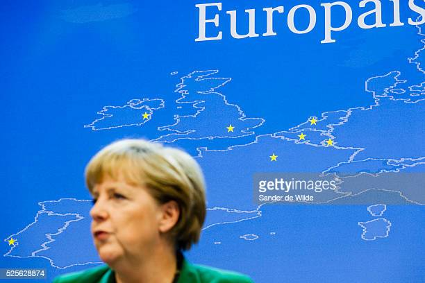 German Chancellor Angela Merkel speaks, with focus on the background, a plan of europe, during a media conference after an EU summit in Brussels on...
