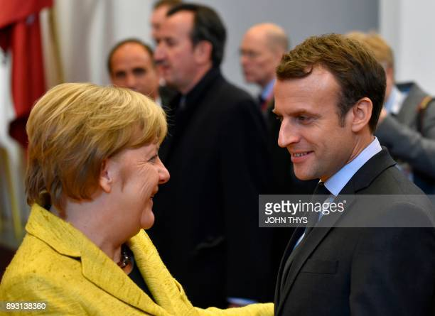 German Chancellor Angela Merkel speaks with French President Emmanuel Macron as they leave on first day of a European Union Summit in Brussels at the...