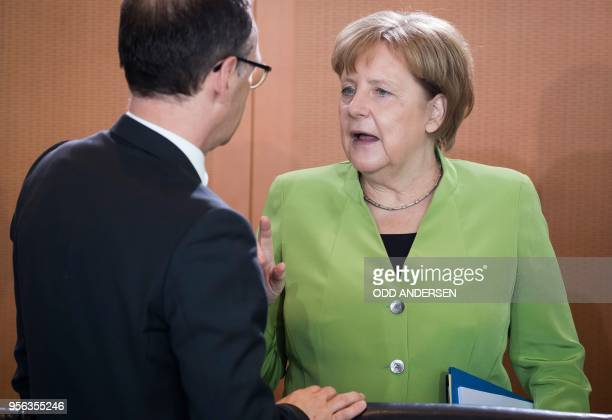 German Chancellor Angela Merkel speaks with German Foreign Minister Heiko Maas at the start of the weekly cabinet meeting at the Chancellery in...