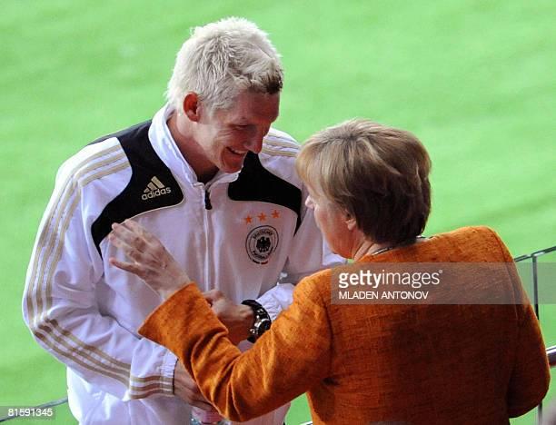 German Chancellor Angela Merkel speaks with German midfielder Bastian Schweinsteiger during the Euro 2008 Championships Group B football match...