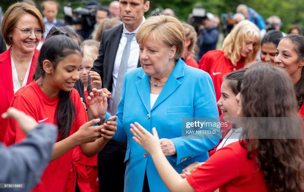 German Chancellor Angela Merkel (C) speaks with girls taking part in the event 'Sports and Integration' as she visits the 'SV Rot-Weiß Viktoria Mitte 08' sports club in Berlin on June 13, 2018, prior to the German government's integration summit. (Photo by Kay Nietfeld / dpa / AFP) / Germany OUT