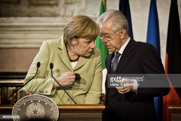 German Chancellor Angela Merkel speaks with Italian Prime Minister Mario Monti during the press conference after the quadrilateral meeting at Villa...