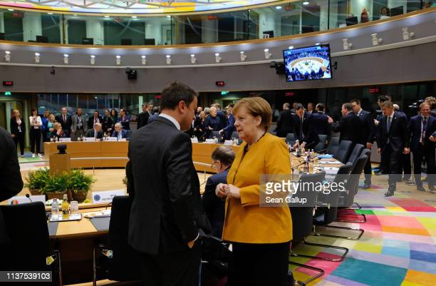 German Chancellor Angela Merkel speaks with Luxembourg Prime Minister Xavier Bettel on the second day of an EU summit on March 22 2019 in Brussels...