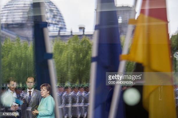 German Chancellor Angela Merkel speaks with one of her advisors as the German parliament building Reichstag and flags are reflected in the window as...