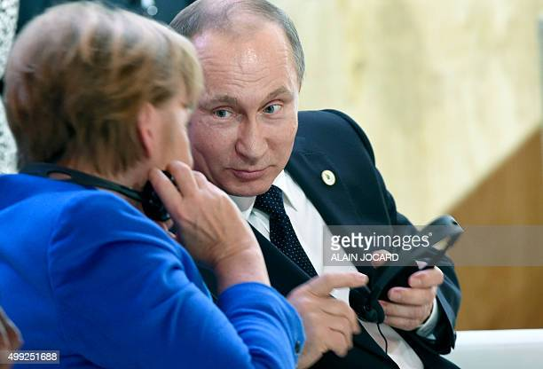 German Chancellor Angela Merkel speaks with Russian President Vladimir Putin during the opening day of the World Climate Change Conference 2015 , on...