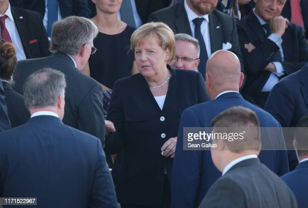 German Chancellor Angela Merkel speaks with US Naitonal Security Advisor John Bolton at an international ceremony to commemorate the 80th anniversary...