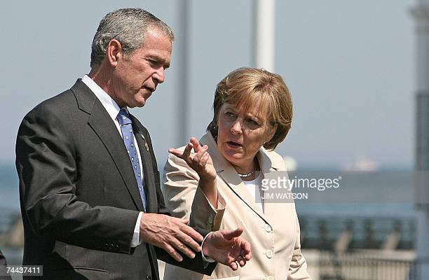 German Chancellor Angela Merkel speaks with US President George W Bush after posing for the family photo with Outreach Nations 08 June 2007 during...