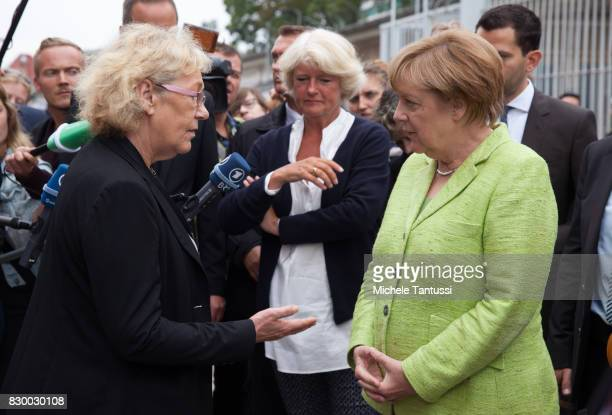 German Chancellor Angela Merkel speaks with visitors as she visits the former prison of the East German communistera secret police or Stasi at...