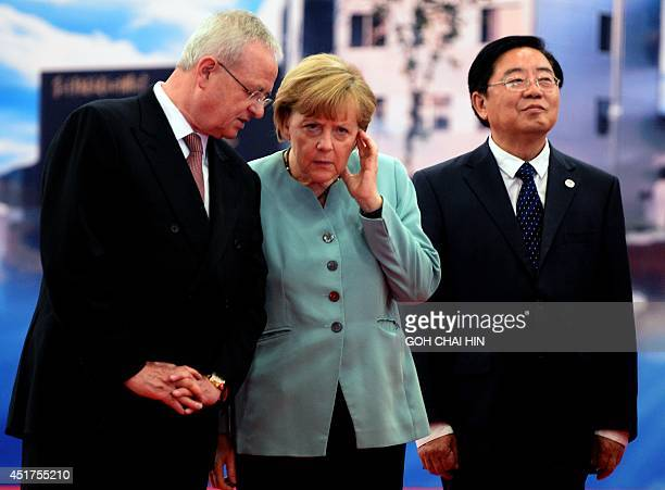 German Chancellor Angela Merkel speaks with Volkswagen CEO Martin Winterkorn as FAW Group CEO Xu Jianyi looks on during her visit to the...