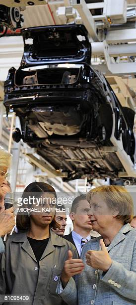 German Chancellor Angela Merkel speaks with Volkswagen employees during a visit to the VW plant in Sao Bernardo do Campo southern Sao Paulo on May 15...