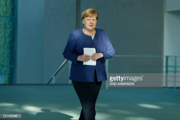 German Chancellor Angela Merkel squints in the sunlight as she arrives to address a press conference following a metting with international economic...