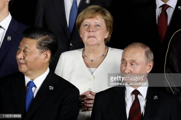 German Chancellor Angela Merkel stands behind Russian President Vladimir Putin and Chinese President Xi Jinping as they arrive to pose for a group...