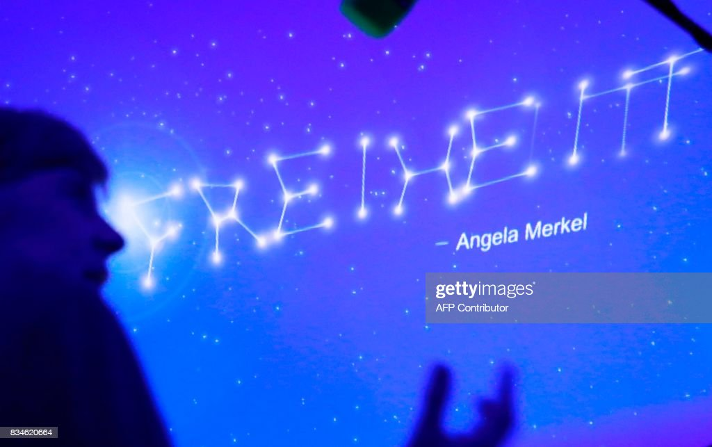 German Chancellor Angela Merkel stands in front of a wall with stars reading 'Liberty' during the opening ceremony of the CDU election campaign exhibition, so-called walkable campaigning program (Das Begehbare Programm) in Berlin, on August 18, 2017. / AFP PHOTO / Odd ANDERSEN / ALTERNATIVE
