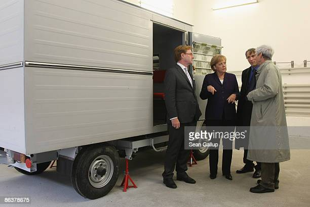 German Chancellor Angela Merkel stands next to a small truck once used for transporting prisoners while touring the former prison of the East German...