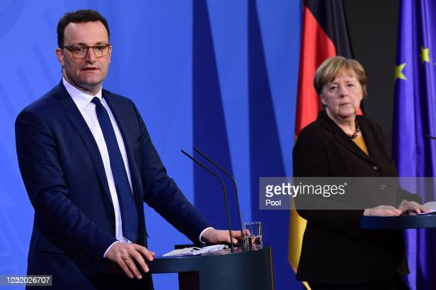 German Chancellor Angela Merkel stands next to German Health Minister Jens Spahn during a joint press conference at the chancellery on March 30, 2021...