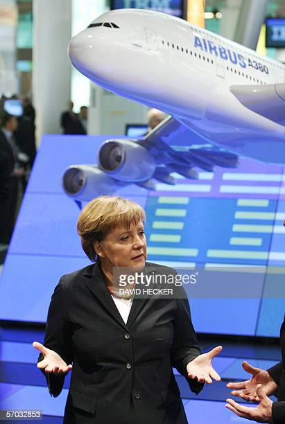 German Chancellor Angela Merkel stands underneath a replica of the Airbus A380 on the IBM stand during her inaugural visit of the 2006 CeBIT...