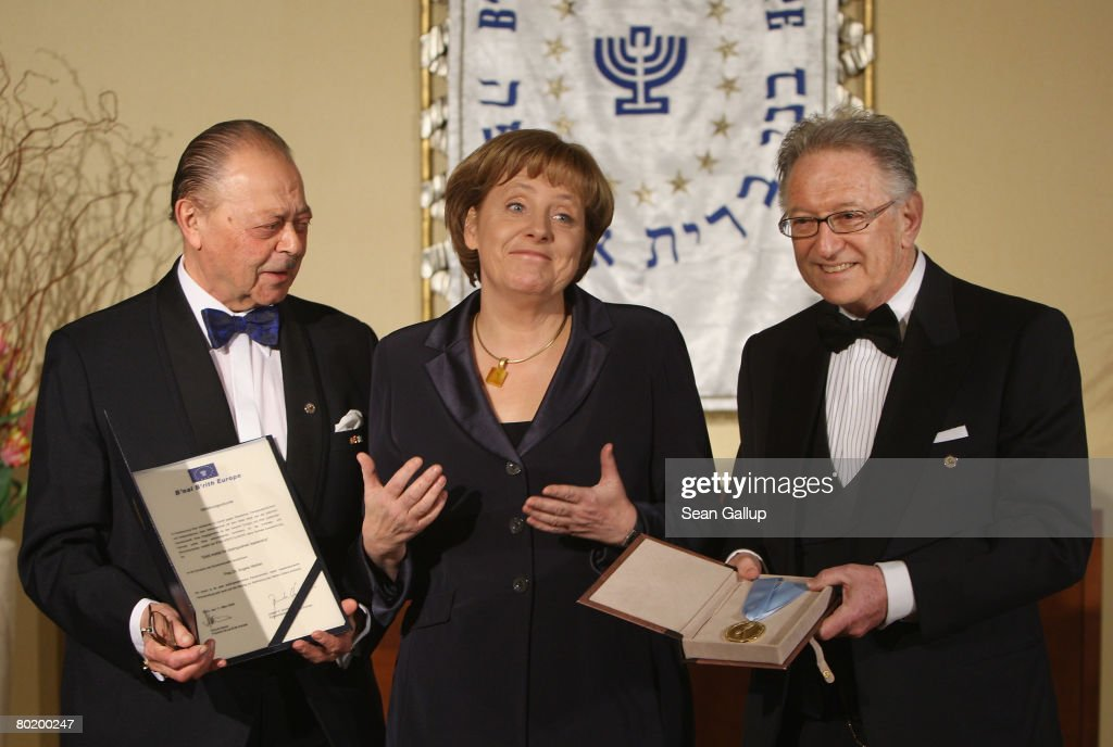 German Chancellor Angela Merkel stands with B'nai B'rith Europe Honourary President Joseph Domberger (L) and B'nai B'rith Europe President Reinold Simon prior to receiving the B'nai B'rith Gold Medal at the B'nai B'rith Europe Award of Merit at the Marriot hotel on March 11, 2008 in Berlin, Germany.