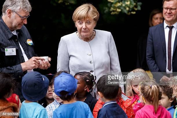 German Chancellor Angela Merkel stands with children on a laboratory station during her visit to the Weydemeyerstrasse Kindergarten on Jne 21 2016 in...