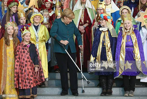 German Chancellor Angela Merkel stands with crutches as she attends a gathering of Epiphany child singers dressed as the Three Kings at the...