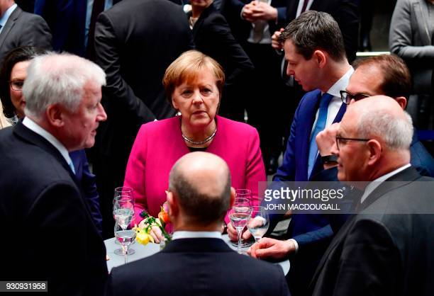 German Chancellor Angela Merkel stands with CSU leader and designated German Interior Minister Horst Seehofer designated German Finance Minister and...