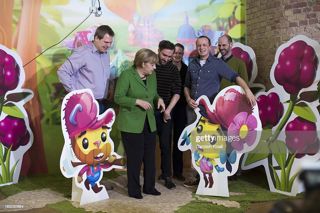 German Chancellor Angela Merkel (2nd L), stays together with artists between characters, during a guided tour by the general manager Jens Begemann (L) at the Wooga company, which makes social games for smartphones and tablets, on March 7, 2013 in Berlin, Germany. Berlin has drawn a significant number of startup companies in recent years, many of which are drawn by the city's hip reputation and its comparatively low cost of living.