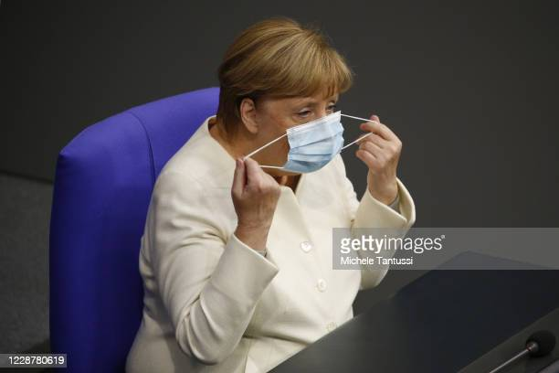 German Chancellor Angela Merkel take off her face mask as she arrives at the plenary room of the germans lower house of Parliament or Bundestag ahead...