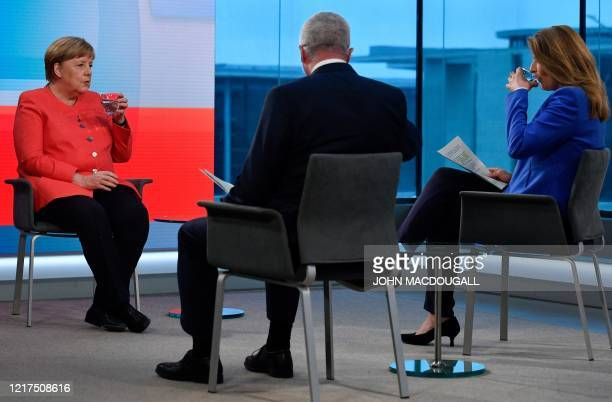 German Chancellor Angela Merkel takes a drink of water as she sits with tv journalists Tina Hassel and Rainald Becker sit ahead of a televised...