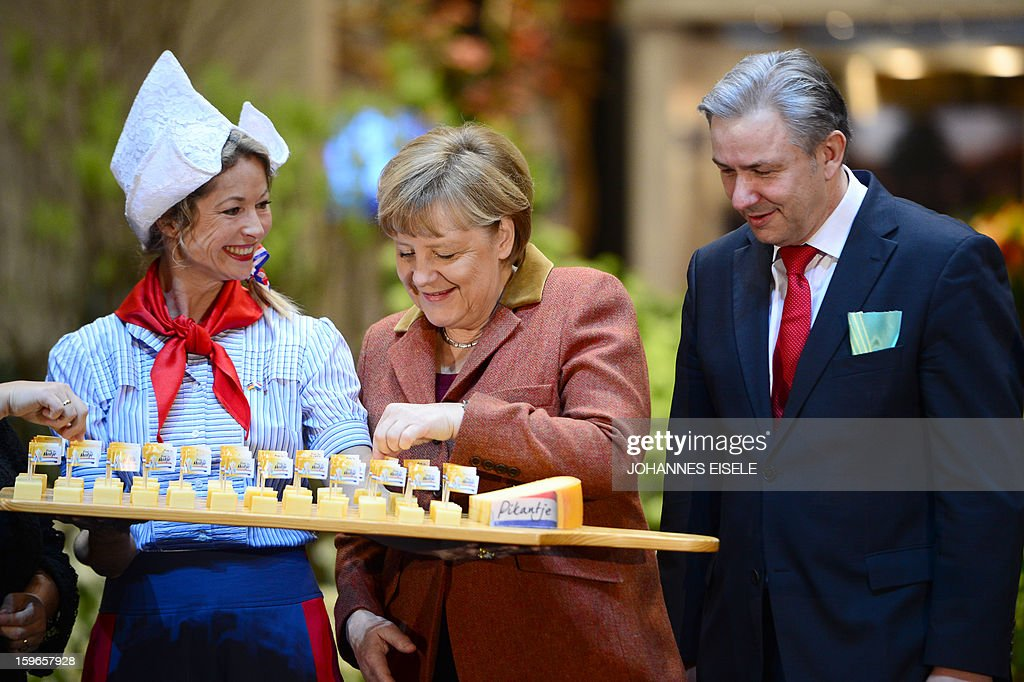 German Chancellor Angela Merkel (C) takes a piece of cheese while visiting the Netherlands booth with Berlin Mayor Klaus Wowereit (R) as she opens the Gruene Woche Agricultural Fair in Berlin on January 18, 2013. This year the official partner country of the fair is The Netherlands. EISELE