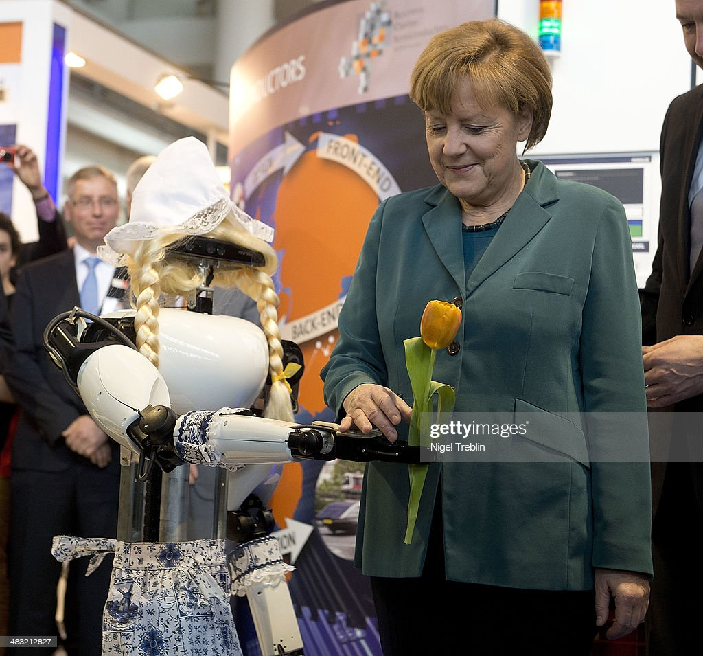 German Chancellor Angela Merkel takes a tulp from a robot at the Hannover Messe industrial trade fair on April 7, 2014 in Hanover, Germany. The Netherlands is the official partner Country of this year's fair with more than 5000 companies showcasing their latest industrial products and solutions. The Hannover Fair will run from April 07-11.