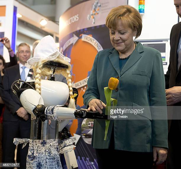 German Chancellor Angela Merkel takes a tulp from a robot at the Hannover Messe industrial trade fair on April 7 2014 in Hanover Germany The...