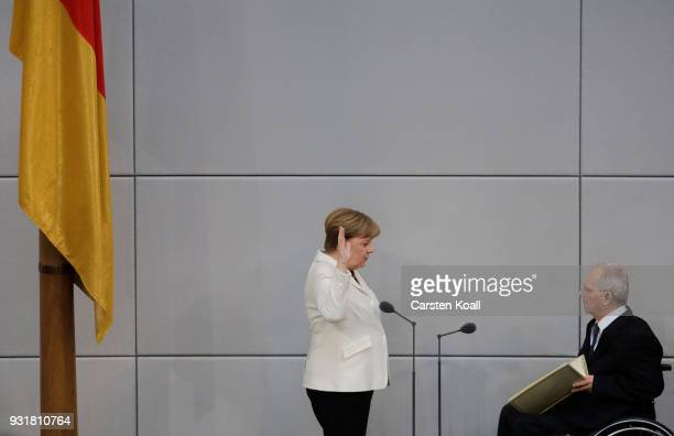 German Chancellor Angela Merkel takes her oath to serve her fourth term as chancellor as Bundestag President Wolfgang Schaeuble holds up a copy of...