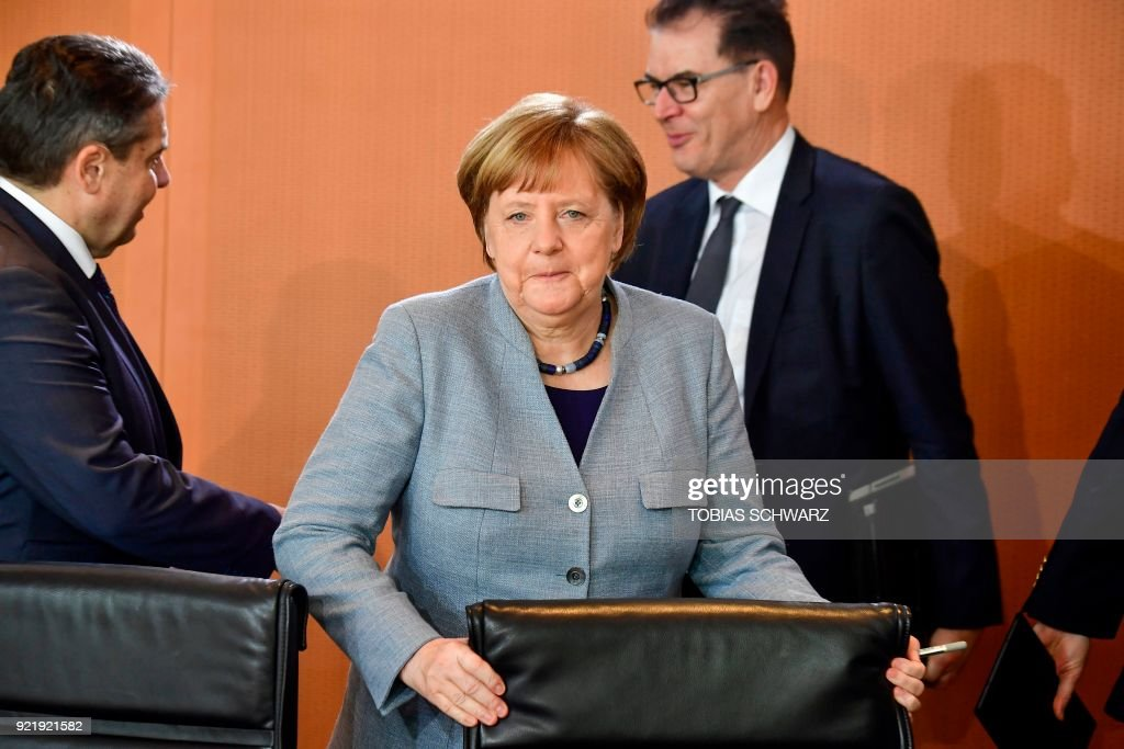 German Chancellor Angela Merkel takes her seat next to German Foreign Minister Sigmar Gabriel (L) prior to the weekly cabinet meeting at the Chancellery in Berlin on February 21, 2018. / AFP PHOTO / Tobias SCHWARZ