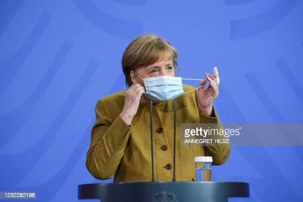 German Chancellor Angela Merkel takes off her face mask as she arrives for a statement in Berlin, on April 13, 2021 amid the novel coronavirus...