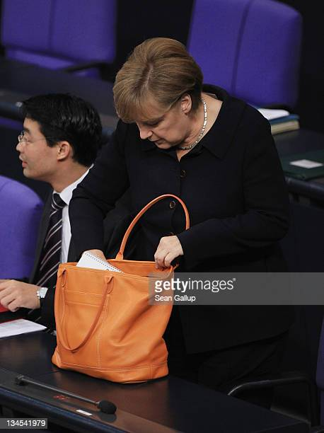German Chancellor Angela Merkel takes out a document from her handbag during debates at the Bundestag before she gave a government declaration on the...
