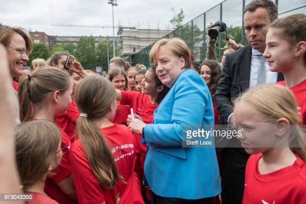 German Chancellor Angela Merkel takes selfies with young girls during a visit of a program to encourage integration of children with foreign roots...